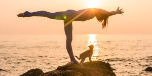 Woman in yoga pose beside the ocean